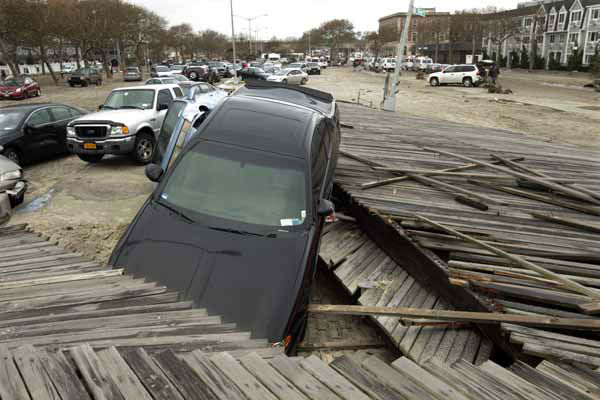 Pedestrians walk past the boardwalk and cars displaced by superstorm Sandy, near Rockaway Beach in the New York City borough of Queens, Tuesday, Oct. 30, 2012, in New York. Sandy, the storm that made landfall Monday, caused multiple fatalities, halted mass transit and cut power to more than 6 million homes and businesses. &#40;AP Photo&#47;Frank Franklin II&#41; <span class=meta>(AP Photo&#47; Frank Franklin II)</span>