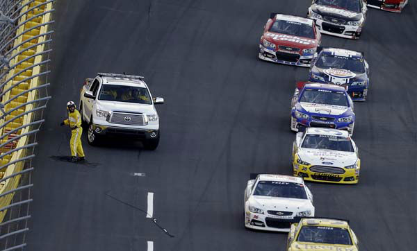 A crew gathers cable from a broken television camera rig as drivers navigate around during the NASCAR Sprint Cup Series Coca-Cola 600 auto race at the Charlotte Motor Speedway in Concord, N.C., Sunday, May 26, 2013. The race was red flagged temporarily and several cars were damaged after running over the cable. &#40;AP Photo&#47;Gerry Broome&#41; <span class=meta>(AP Photo&#47; Gerry Broome)</span>