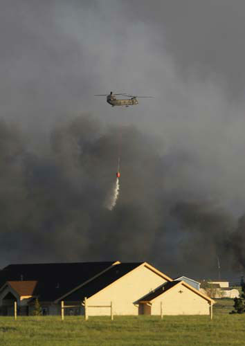 A U.S. Army helicopter drops a load of water on a wildfire in the Black Forest area north of Colorado Springs, Colo., on Tuesday, June 11, 2013. At least four major wildfires broke out along the front of the Rocky Mountains in Colorado Tuesday, burning a handful of houses and chasing people from thousands of homes in hot, gusty weather. &#40;AP Photo&#47;Ed Andrieski&#41; <span class=meta>(AP Photo&#47; Ed Andrieski)</span>