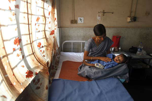 A hospital worker cares for a 10-month-old child injured in a building collapse, at a hospital on the outskirts of Mumba, India, Friday, April 5, 2013. The residential building being constructed illegally on forest land in a suburb of India&#39;s financial capital collapsed into a mound of steel and concrete, killing at least 41 people and injuring more than 50 others, authorities said Friday. &#40;AP Photo&#47;Rajanish Kakade&#41; <span class=meta>(AP Photo&#47; Rajanish Kakade)</span>