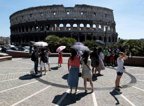 Tourists take pictures in front of Rome&#39;s Colosseum, Tuesday, July 31, 2012. Italian cultural officials say a &#40;euro&#41; 25-million &#40;&#36;30-million&#41; restoration of the Colosseum being paid for by founder of luxury shoemaker Tod&#39;s Diego Della Valle,  will begin in December. Officials announced Tuesday that the work is expected to take 2 1&#47;2 years. The ancient Roman arena has been blackened by pollution and rocked by vibrations from a nearby subway line. &#40;AP Photo&#47;Gregorio Borgia&#41; <span class=meta>(AP Photo&#47; Gregorio Borgia)</span>
