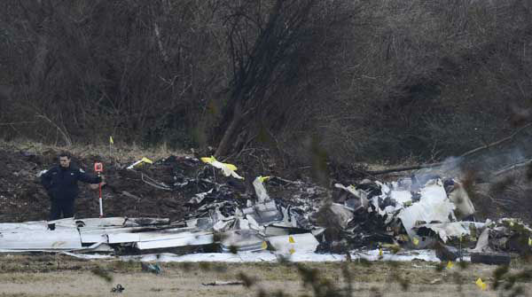 Investigators examine the site of a plane crash Tuesday, Feb. 4, 2014 near Nashville.  The small plane crashed on Monday,  near a YMCA in suburban Nashville, killing everyone on board and damaging cars in the parking lot. Authorities believe four members of the same family were on board the flight, which crashed near in Bellevue.   The Gulfstream 690C departed from Great Bend Municipal Airport in Great Bend, Kansas, Monday afternoon around 2:45 p.m.,  and crashed 16 kilometres south of John C. Tune Airport in Nashville about 5 p.m.  &#40;AP Photo&#47;Mark Zaleski&#41; <span class=meta>(Photo&#47;Mark Zaleski)</span>