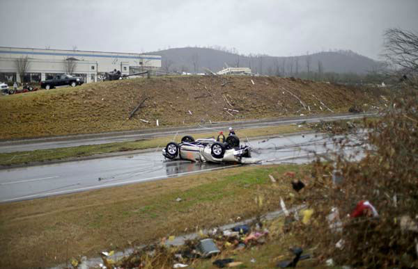 Tommy Stouffer, right, looks at his overturned car with his son Jonathan, 11, after a tornado picked it up from the parking lot where he was working across the street and dumped it in the middle of the road, Wednesday, Jan. 30, 2013, in Adairsville, Ga. A fierce storm system that roared across Georgia has left at least one person dead after it demolished buildings and flipped vehicles on Interstate 75 northwest of Atlanta. &#40;AP Photo&#47;David Goldman&#41; <span class=meta>(AP Photo&#47; David Goldman)</span>
