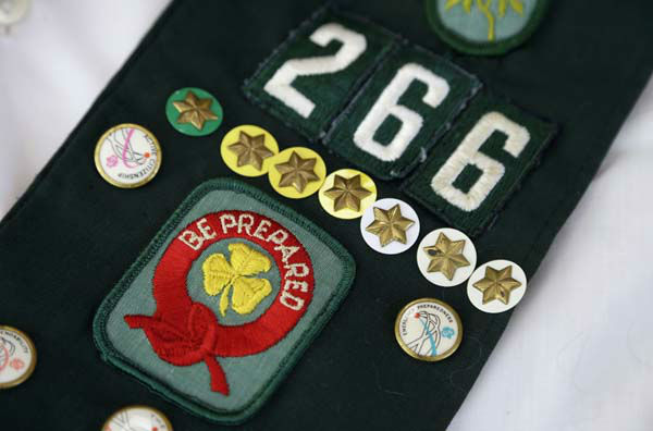 This Tuesday, May 14, 2013 photo shows pins on the childhood Girl Scouts sash of Joni Kinsey, in Iowa City, Iowa. In an effort to save money, Girl Scout councils across the country are making proposals that would have been unthinkable a generation ago: selling summer camps that date back to the 1950s. &#40;AP Photo&#47;Charlie Neibergall&#41; <span class=meta>(AP Photo&#47; Charlie Neibergall)</span>