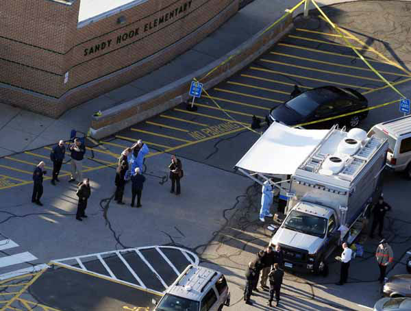 Officials are on the scene outside of Sandy Hook Elementary School in Newtown, Conn., where authorities say a gunman opened fire inside an elementary school in a shooting that left 27 people dead, including 20 children, Friday, Dec. 14, 2012. &#40;AP Photo&#47;Julio Cortez&#41; <span class=meta>(AP Photo&#47; Julio Cortez)</span>
