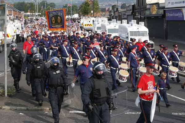 Britain Northern Ireland Orange Parade  Riot police escort a loyalist band past the Ardoyne area of North Belfast, Northern Ireland, Friday, July 12, 2013. A large security operation swung into place as a controversial Protestant Orange Order march passed the Catholic Ardoyne area.  <span class=meta>(AP Photo&#47;Peter Morrison&#41; )</span>