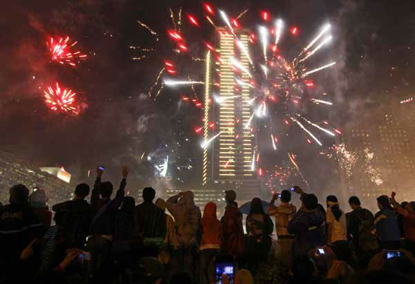 Indonesians watch firework explode on New Year&#39;s eve in Jakarta, Indonesia, late Monday, Dec. 31, 2012. &#40;AP Photo&#47;Dita Alangkara&#41; <span class=meta>(AP Photo&#47; Dita Alangkara)</span>