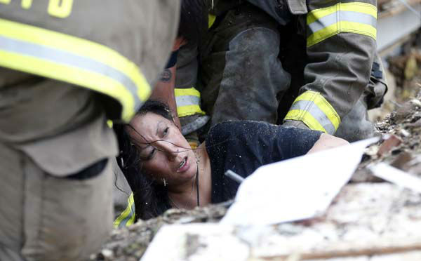 A woman is pulled out from under tornado debris at the Plaza Towers School in Moore, Okla., Monday, May 20, 2013. A tornado as much as a mile &#40;1.6 kilometers&#41; wide with winds up to 200 mph &#40;320 kph&#41; roared through the Oklahoma City suburbs Monday, flattening entire neighborhoods, setting buildings on fire and landing a direct blow on an elementary school. &#40;AP Photo Sue Ogrocki&#41; <span class=meta>(AP Photo&#47; Sue Ogrocki)</span>