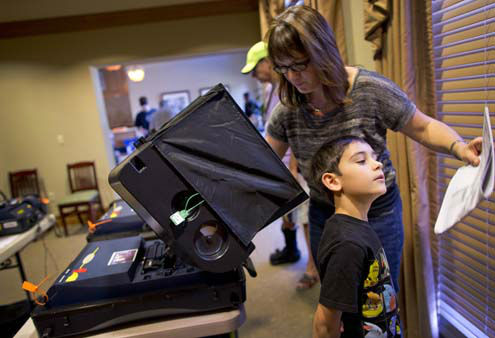 "<div class=""meta ""><span class=""caption-text "">Enzo Valenti, 7,right, looks over his mother, Michelle Valenti's sample ballot as she casts her votes on Election Day, Tuesday, Nov. 6, 2012, in Las Vegas. After a grinding presidential campaign President Barack Obama and Republican presidential candidate, former Massachusetts Gov. Mitt Romney, yield center stage to American voters Tuesday for an Election Day choice that will frame the contours of government and the nation for years to come. (AP Photo/Julie Jacobson) (AP Photo/ Julie Jacobson)</span></div>"