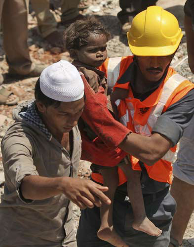 Indian rescue workers carry a young child who survived a building collapse on the outskirts of Mumbai, India, Friday, April 5, 2013. The half-finished building that was being constructed illegally in a suburb of India&#39;s financial capital collapsed on Thursday, killing 35 people and injuring more than 50 others, police said Friday. &#40;AP Photo&#41; <span class=meta>(AP Photo&#47; RK MS SXJ TT**TOK**)</span>
