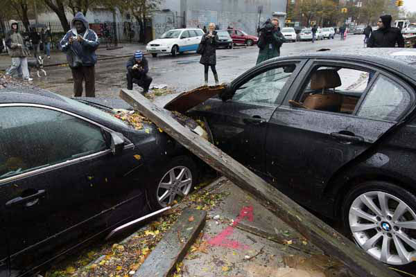 Onlookers take photographs of two cars that collided during flooding outside the Consolidated Edison power sub-station on 14th Street, Tuesday, Oct. 30, 2012, in New York. Hurricane Sandy marched slowly inland, leaving millions without power or mass transit, with huge swatches of the nation&#39;s largest city unusually vacant and dark. New York was among the hardest hit, with its financial heart in Lower Manhattan shuttered for a second day and seawater cascading into the still-gaping construction pit at the World Trade Center &#40;AP Photo&#47; John Minchillo&#41; <span class=meta>(AP Photo&#47; John Minchillo)</span>