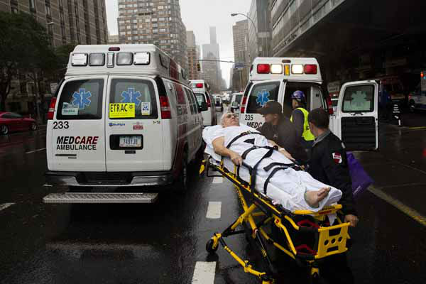 A patient is wheeled to an ambulance in the rain during an evacuation of New York University Tisch Medical, Tuesday, Oct. 30, 2012, in New York. Hurricane Sandy marched slowly inland, leaving millions without power or mass transit, with huge swatches of the nation&#39;s largest city unusually vacant and dark. New York was among the hardest hit, with its financial heart in Lower Manhattan shuttered for a second day and seawater cascading into the still-gaping construction pit at the World Trade Center. &#40;AP Photo&#47; John Minchillo&#41; <span class=meta>(AP Photo&#47; John Minchillo)</span>