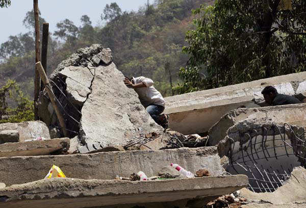 Indian men search for survivors in the debris of a building that collapsed on the outskirts of Mumbai, India, Friday, April 5, 2013. The half-finished building that was being constructed illegally in a suburb of India&#39;s financial capital collapsed on Thursday, killing 35 people and injuring more than 50 others, police said Friday. &#40;AP Photo&#47;Rajanish Kakade&#41; <span class=meta>(AP Photo&#47; Rajanish Kakade)</span>