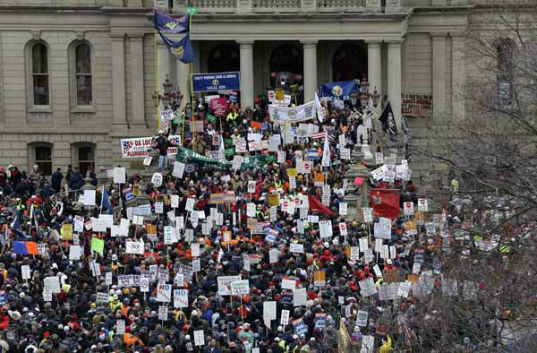 Protesters gather for a rally at the State Capitol in Lansing, Mich., Tuesday, Dec. 11, 2012. The crowd is protesting right-to-work legislation passed last week. Michigan could become the 24th state with a right-to-work law next week. Rules required a five-day wait before the House and Senate vote on each other&#39;s bills; lawmakers are scheduled to reconvene Tuesday and Gov. Snyder has pledged to sign the bills into law. &#40;AP Photo&#47;Paul Sancya&#41; <span class=meta>(Photo&#47;Paul Sancya)</span>