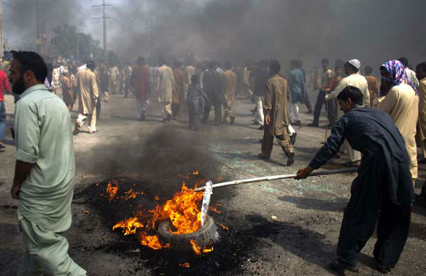 Pakistani protesters burn tires to block the main highway in Rawalpindi, Pakistan on Friday, Sept. 21, 2012. Pakistan has blocked cell phone service in major cities to prevent militants from using phones to detonate bombs during a national day of protest against an anti-Islam film produced in the United States. &#40;AP Photo&#47;B.K. Bangash&#41; <span class=meta>(AP Photo&#47; B.K. Bangash)</span>