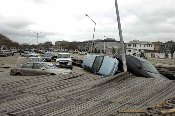 Pedestrians walk past the boardwalk and cars displaced by superstorm Sandy, near Rockaway Beach in the New York City borough of Queens Tuesday, Oct. 30, 2012, in New York. Sandy, the storm that made landfall Monday, caused multiple fatalities, halted mass transit and cut power to more than 6 million homes and businesses. &#40;AP Photo&#47;Frank Franklin II&#41; <span class=meta>(AP Photo&#47; Frank Franklin II)</span>
