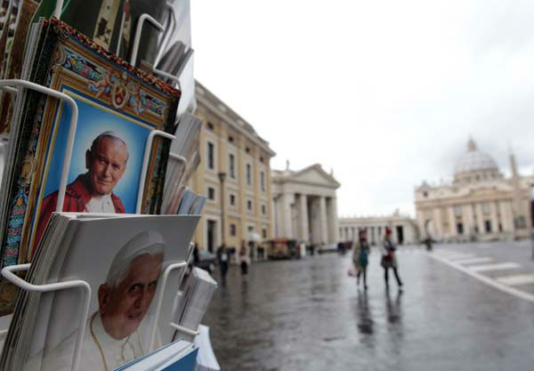 Postcards of Pope Benedict XVI, bottom, and late Pope John Paul II, are displayed outside a kiosk with St. Peter&#39;s Basilica in the background, at the Vatican, Monday, Feb. 11, 2013. Pope Benedict XVI announced Monday that he would resign Feb. 28 ? the first pontiff to do so in nearly 600 years. The decision sets the stage for a conclave to elect a new pope before the end of March. &#40;AP Photo&#47;Gregorio Borgia&#41; <span class=meta>(AP Photo&#47; Gregorio Borgia)</span>