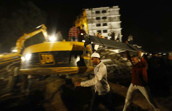 Rescue workers carry a stretcher near the  site where  a residential building collapsed in Thane, Mumbai, India, Thursday, April 4, 2013. At least 6 persons were killed and 40 were injured when an under construction residential building collapsed on Thursday evening according to local reports.&#40;AP Photo&#47;Rafiq Maqbool&#41; <span class=meta>(AP Photo&#47; Rafiq Maqbool)</span>