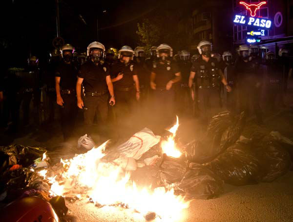 Turkish riot police stand by a burning barricade during clashes with protesters in Ankara, Turkey, Tuesday, June 11, 2013. Turkey&#39;s Prime Minister Recep Tayyip Erdogan will meet with a group of protesters occupying Istanbul&#39;s central Taksim Square this week, Deputy Prime minister Bulent Arinc said Monday, as the government sought a way out of the impasse that has led to hundreds of protests in dozens of cities.  &#40;AP Photo&#47;Vadim Ghirda&#41; <span class=meta>(AP Photo&#47; Vadim Ghirda)</span>