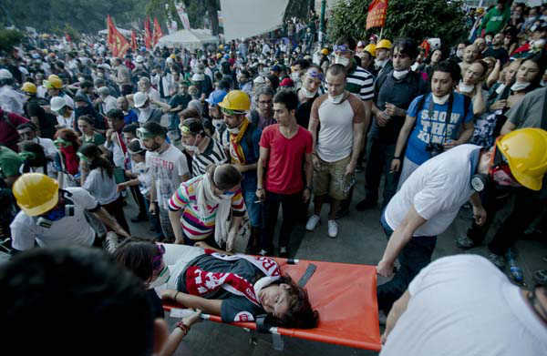 "<div class=""meta image-caption""><div class=""origin-logo origin-image ""><span></span></div><span class=""caption-text"">A girl is evacuated on a stretcher after riot police flooded the Gazi Park with tear gas during clashes at the Taksim Square in Istanbul Tuesday, June 11, 2013. Riot police are re-entering Istanbul?s Taksim Square after defiant protesters swarmed back in by the thousands. Massive plumes of tear gas billowed upward, and police fired water cannons Tuesday night. (AP Photo/Vadim Ghirda) (AP Photo/ Vadim Ghirda)</span></div>"