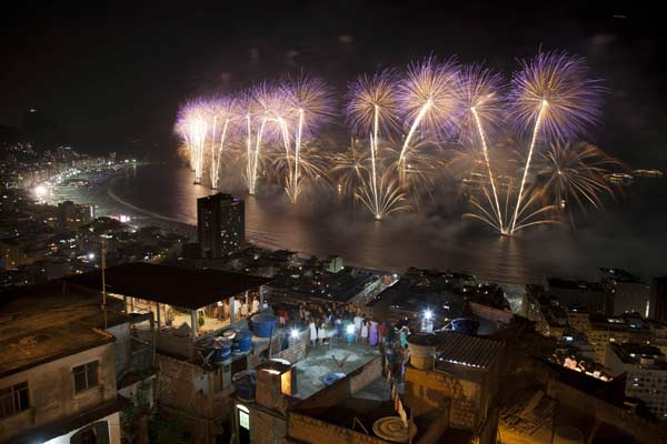People watch fireworks exploding over Copacabana beach during New Year celebrations at the Pavao Pavaozinho slum in Rio de Janeiro, Brazil, Tuesday, Jan. 1, 2013. (AP Photo/Felipe Dana)