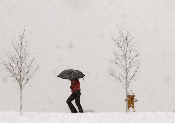 A person walks along Jayhawk Boulevard with an umbrella as snow from a winter storm begins to fall in Lawrence, Kan., Saturday, March 23, 2013. &#40;AP Photo&#47;Orlin Wagner&#41; <span class=meta>(AP Photo&#47; Orlin Wagner)</span>