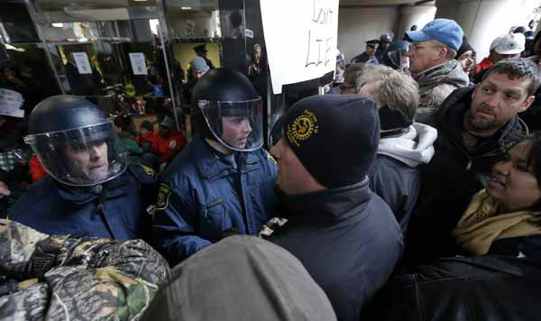 Michigan State Police push protesters away from the entrance of the George W. Romney State Building, where Gov. Snyder has an office in Lansing, Mich., Tuesday, Dec. 11, 2012. The crowd is protesting right-to-work legislation passed last week. Michigan could become the 24th state with a right-to-work law next week. Rules required a five-day wait before the House and Senate vote on each other&#39;s bills; lawmakers are scheduled to reconvene Tuesday and Gov. Snyder has pledged to sign the bills into law. &#40;AP Photo&#47;Paul Sancya&#41; <span class=meta>(AP Photo&#47; Paul Sancya)</span>