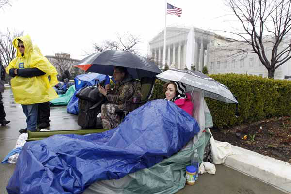 Sabrina Canela from Arizona, covers up from the snow while waiting in line outside the Supreme Court in Washington, Monday March, 25, 2013, a day before the court will hear a same-sex marriage case. &#40;AP Photo&#47;Jose Luis Magana&#41; <span class=meta>(AP Photo&#47; Jose Luis Magana)</span>