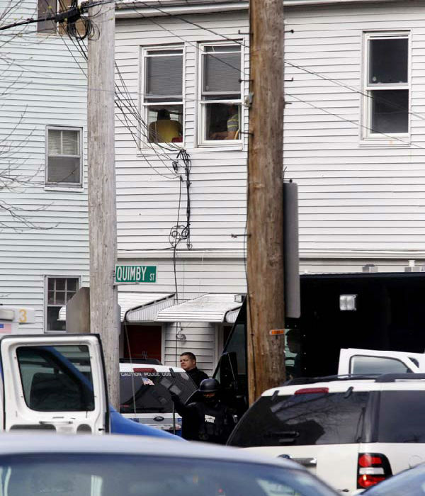 Residents are seen near a window, top, as an official wearing tactical gear stands guard while searching for an individual believed to be involved in the Boston Marathon explosions in Watertown, Mass., Friday, April 19, 2013. Two suspects in the Boston Marathon bombing killed an MIT police officer, injured a transit officer in a firefight and threw explosive devices at police during a getaway attempt in a long night of violence that left one of them dead and another still at large Friday, authorities said as the manhunt intensified for a young man described as a dangerous terrorist.  &#40;AP Photo&#47;Julio Cortez&#41; <span class=meta>(AP Photo&#47; Julio Cortez)</span>