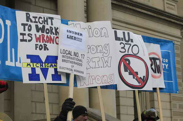 Protesters stand and block a right-to-work banner on the State Capitol grounds in Lansing, Mich., Tuesday, Dec. 11, 2012. The crowd is protesting right-to-work legislation that was passed by the state legislature last week. &#40;AP Photo&#47;Carlos Osorio&#41; <span class=meta>(AP Photo&#47; Carlos Osorio)</span>