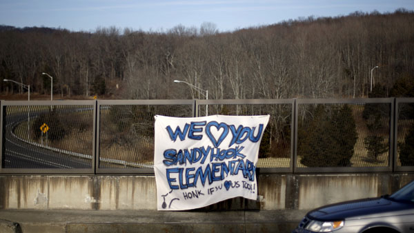 A banner hangs from an overpass encouraging passing motorists to honk their horns in support of the Sandy Hook Elementary School shooting victims, Saturday, Dec. 15, 2012, in Newtown, Conn. The massacre of 26 children and adults at Sandy Hook Elementary school elicited horror and soul-searching around the world even as it raised more basic questions about why the gunman, 20-year-old Adam Lanza, would have been driven to such a crime and how he chose his victims. (AP Photo/David Goldman)