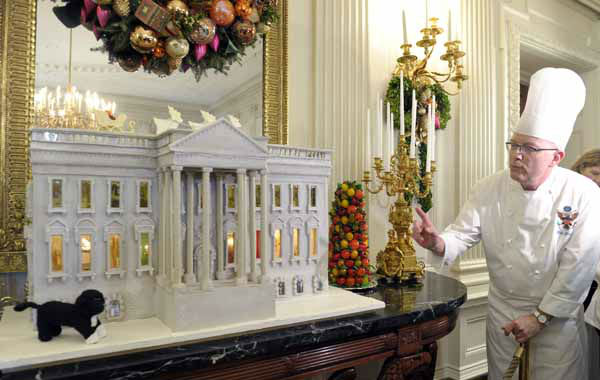 White House Pastry Chef Bill Yosses explains his design for the nearly 300-pound gingerbread house of the White House, on display in the State Dining Room of the White House in Washington, Wednesday, Nov. 28, 2012. The house features Bo, the Obama family dog, left,  a vegetable garden and views inside the White House. The theme for the White House Christmas 2012 is Joy to All. The White House gingerbread house has been a tradition since the 1960s. &#40;AP Photo&#47;Susan Walsh&#41; <span class=meta>(AP Photo&#47; Susan Walsh)</span>