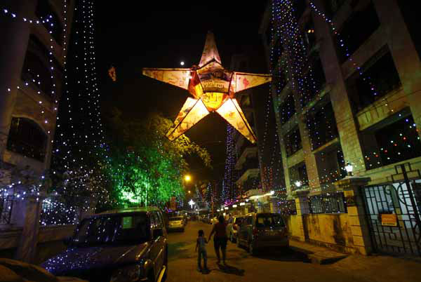 A woman with her daughter walks in a decorated street with lights to celebrate the New Year in Mumbai, India, Tuesday, Jan. 1, 2013.&#40;AP Photo&#47;Rafiq Maqbool&#41; <span class=meta>(AP Photo&#47; Rafiq Maqbool)</span>