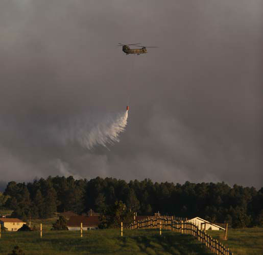 "<div class=""meta ""><span class=""caption-text "">A U.S. Army helicopter drops a load of water on a wildfire in the Black Forest area north of Colorado Springs, Colo., on Tuesday, June 11, 2013. At least four major wildfires broke out along the front of the Rocky Mountains in Colorado Tuesday, burning a handful of houses and chasing people from thousands of homes in hot, gusty weather. (AP Photo/Ed Andrieski) (AP Photo/ Ed Andrieski)</span></div>"