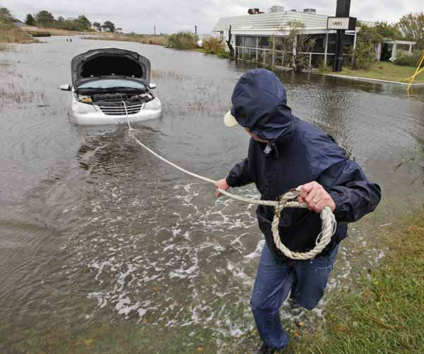 Glenn Heartley pulls on a rope attached to his car in preparation for getting it towed from a creek in Chincoteague, Va., Tuesday, Oct. 30, 2012. Heartley and his wife were swept off the road into the shallow creek during superstorm Sandy&#39;s arrival Monday. &#40;AP Photo&#47;Steve Helber&#41; <span class=meta>(AP Photo&#47; Steve Helber)</span>