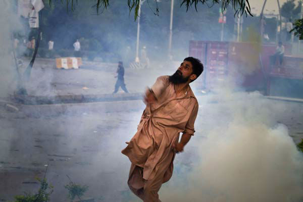 A Pakistani protester hurls back a tear gas canister fired by police, not pictured, during clashes that erupted as protestors tried to approach the U.S. embassy, in Islamabad, Pakistan, Thursday, Sept. 20, 2012. Hundreds of Pakistanis angry at an anti-Islam film that denigrates the religion&#39;s prophet clashed with police in the Pakistani capital Thursday, the most violent show of anger in a day that saw smaller demonstrations in Indonesia, Iran and Afghanistan. &#40;AP Photo&#47;Anjum Naveed&#41; <span class=meta>(AP Photo&#47; Anjum Naveed)</span>