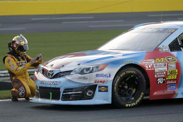 Kyle Busch takes a photo of his damaged race car with his phone camera during a red flag in the NASCAR Sprint Cup series Coca-Cola 600 auto race at Charlotte Motor Speedway in Concord, N.C., Sunday, May 26, 2013. &#40;AP Photo&#47;Nell Redmond&#41; <span class=meta>(AP Photo&#47; Nell Redmond)</span>