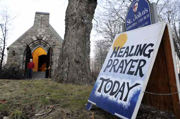 A sign for a Healing Prayer stands outside St. John&#39;s Episcopal Church near the scene of a school shooting in Newtown, Conn., Friday, Dec. 14, 2012.  A man opened fire Friday inside two classrooms at the school where his mother worked as a teacher, killing 26 people, including 20 children.  The killer, armed with two handguns, committed suicide at the school and another person was found dead at a second scene, bringing the toll to 28, authorities said. A law enforcement official identified the gunman as 20-year-old Adam Lanza.  &#40;AP Photo&#47;Jessica Hill&#41; <span class=meta>(AP Photo&#47; Jessica Hill)</span>