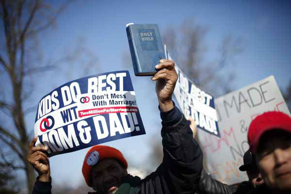 "<div class=""meta image-caption""><div class=""origin-logo origin-image ""><span></span></div><span class=""caption-text"">A demonstrator holds a bible while marching outside the Supreme Court in Washington, Tuesday, March 26, 2013, as the court heard arguments on California's voter approved ban on same-sex marriage, Proposition 8. The Supreme Court waded into the fight over same-sex marriage Tuesday, at a time when public opinion is shifting rapidly in favor of permitting gay and lesbian couples to wed, but 40 states don't allow it.  (AP Photo/Pablo Martinez Monsivais) (AP Photo/ Pablo Martinez Monsivais)</span></div>"