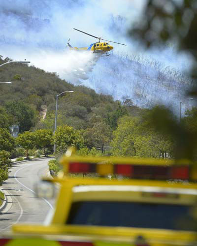 A helicopter makes a water drop on flames as a wildfire burns along a hillside in Thousand Oaks, Calif., Thursday, May 2, 2013. A Ventura County Fire Department spokeswoman said the blaze that broke out Thursday morning near Camarillo and Thousand Oaks, 50 miles west of Los Angeles, had spread to over 6,500 acres, forcing evacuations of nearby neighborhoods. &#40;AP Photo&#47;Mark J. Terrill&#41; <span class=meta>(AP Photo&#47; Mark J. Terrill)</span>