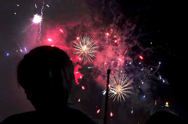 A man is silhouetted as firework explode over the Singapore financial district to mark the start of the new year on Tuesday Jan. 1, 2013 in Singapore. &#40;AP Photo&#47;Wong Maye-E&#41; <span class=meta>(AP Photo&#47; Wong Maye-E)</span>