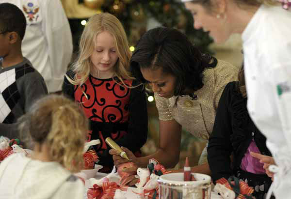 First lady Michelle Obama decorates a lollipop during a holiday decoration preview at the White House in Washington, Wednesday, Nov. 28, 2012. Obama joined school children as they decorated holiday treats. &#40;AP Photo&#47;Susan Walsh&#41; <span class=meta>(Photo&#47;Susan Walsh)</span>