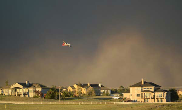A slurry bomber flies over homes as it prepares to drop fire retardant on the Black Forest Fire in northeast of Colorado Springs on Tuesday, June 11, 2013. The fire consumed an estimated 7500 acres. It damaged 40-60 structures and forced the evacuation of thousands of people. As of Tuesday night the fire was reported as zero percent contained. &#40;AP Photo&#47;BryanOller&#41; <span class=meta>(AP Photo&#47; Bryan Oller)</span>