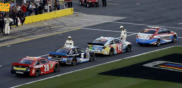 Officials gather around Kyle Busch &#40;18&#41;, Kasey Kahne &#40;5&#41; and Matt Kenseth &#40;20&#41; during a red flag caused by a broken television camera cable rig potentially damaging cars during the NASCAR Sprint Cup Series Coca-Cola 600 auto race at Charlotte Motor Speedway in Concord, N.C., Sunday, May 26, 2013. &#40;AP Photo&#47;Gerry Broome&#41; <span class=meta>(AP Photo&#47; Gerry Broome)</span>