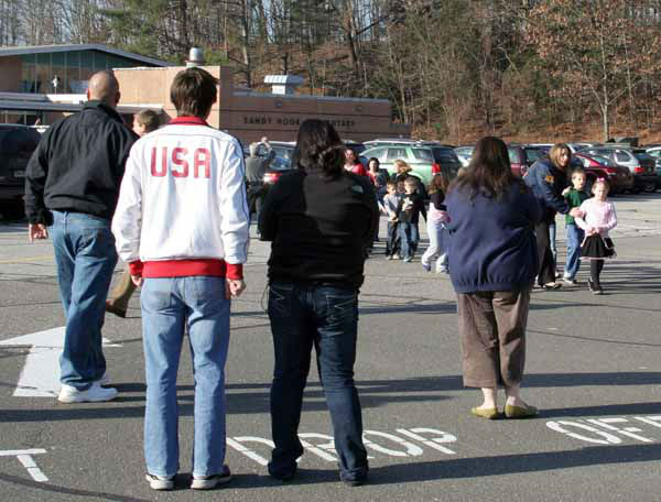 In this photo provided by the Newtown Bee, people look on as students are led out of Sandy Hook Elementary School in Newtown, Conn., where authorities say a gunman opened fire, killing 26 people, including 20 children, Friday, Dec. 14, 2012. &#40;AP Photo&#47;Newtown Bee, Shannon Hicks&#41; MANDATORY CREDIT: NEWTOWN BEE, SHANNON HICKS <span class=meta>(AP Photo&#47; Shannon Hicks)</span>