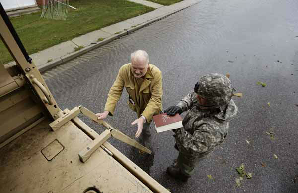 Maryland National Guard Sgt. Zachary Greene holds a bible for Harold &#34;Doc&#34; Sterling as he prepares to climb the ladder into a National Guard truck to be evacuated from his home after the effects of superstorm Sandy Tuesday, Oct. 30, 2012, in Crisfield, Md. &#40;AP Photo&#47;Alex Brandon&#41; <span class=meta>(AP Photo&#47; Alex Brandon)</span>