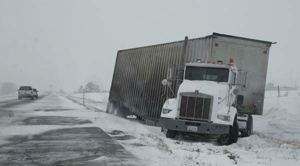 A tractor-trailer sits on the shoulder of Interstate 70 westbound after sliding off the icy highway near Watkins, Colo., as a spring storm packing high winds and heavy snow sweeps over Colorado&#39;s Front Range and on to the eastern plains on Saturday, March 23, 2013. Forecasters predict up to a foot of snow will fall in some locations in Colorado before the storm heads toward the nation&#39;s midsection. &#40;AP Photo&#47;David Zalubowski&#41; <span class=meta>(AP Photo&#47; David Zalubowski)</span>