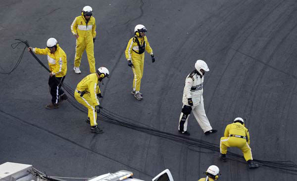 A crew gathers cable from a broken television camera rig during the NASCAR Sprint Cup Series Coca-Cola 600 auto race at the Charlotte Motor Speedway in Concord, N.C., Sunday, May 26, 2013. The race was red flagged temporarily and several cars were damaged after running over the cable. &#40;AP Photo&#47;Gerry Broome&#41; <span class=meta>(AP Photo&#47; Gerry Broome)</span>