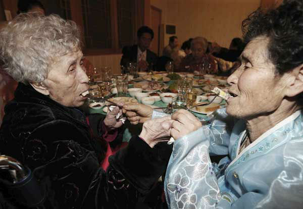South Korean Lee Young-shil, 87, left, and her North Korean daughter Dong Myung-sook, 66, give food each other in a dinner during the Separated Family Reunion Meeting at Diamond Mountain resort in North Korea, Thursday, Feb. 20, 2014. Elderly North and South Koreans separated for six decades are tearfully reuniting, grateful to embrace children, brothers, sisters and spouses they had thought they might never see again. &#40;AP Photo&#47;Yonhap, Lee Ji-eun&#41;  KOREA OUT <span class=meta>(Photo&#47;Lee Ji-eun)</span>