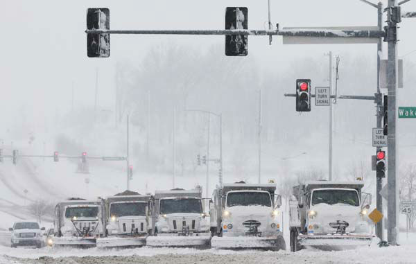 Snow plows stop for a traffic signal as they clear several lanes of West 6th Street in Lawrence, Kan., Sunday, March 24, 2013. Few signs of spring are being found in parts of the Midwest as a snowstorm brings heavy snow and high winds. &#40;AP Photo&#47;Orlin Wagner&#41; <span class=meta>(AP Photo&#47; Orlin Wagner)</span>
